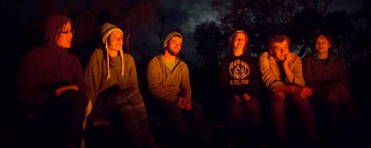 Campers sitting around campfire.